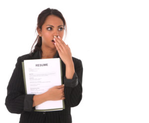 Image of a woman holding a resume, looking shocked at what she's heard