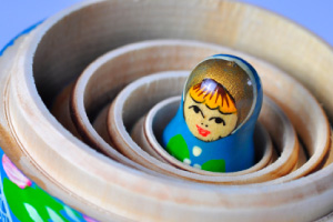 Picture of small wooden doll, at the heart of a set of russian matroshyka dolls