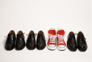 Picture of lined up black work shoes - with a pair of red converse sneakers standing out, in the middle