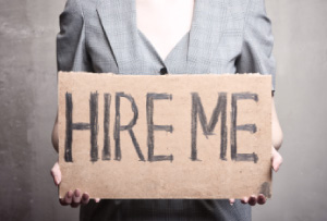 Picture of a career woman holding a 'hire me' sign