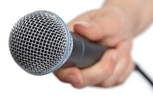 Interviewer holding a microphone, asking a job applicant if they have any questions for the interview panel